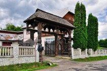 Drewniana brama przed murowanym domem