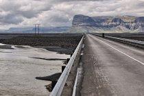 Jeden z wielu mostów, w oddali góra Lómagnúpur