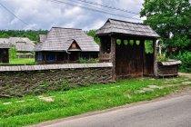 Płot, brama i drewiany dom